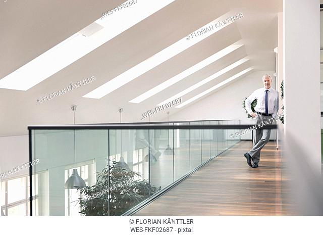 Serene businessman standing in office, smiling