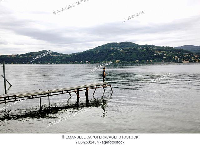 Child on a pier holding fishing rod, Lake Maggiore, Italy