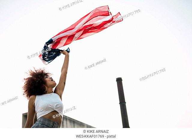 Young woman waving American flag