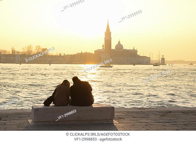 Couple of tourists admire the sunset towards the island of San Giorgio maggiore from the banks of the Grand Canal, Venice, Veneto, Italy