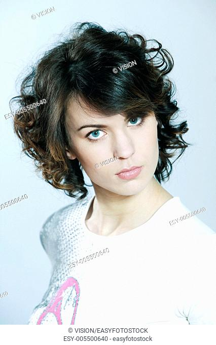studio shots portrait of a beautiful caucasian young serious woman on blue background