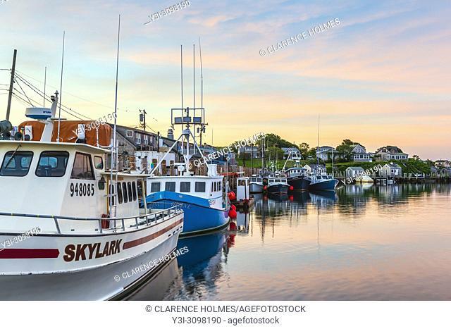 Commercial fishing boats docked in Menemsha Basin under a colorful pre-sunrise sky, in the fishing village of Menemsha in Chilmark