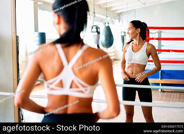 Back view of fit woman looking at herself in mirror at gym. Sport concept