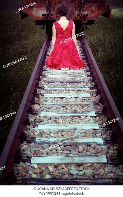 a girl in a red dress is sitting on railway tracks in front of a waggon