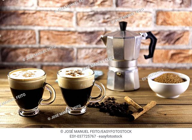 two cup of coffee, Italian coffee maker, coffee beans, cinnamon, napkin and brown sugar bowl on wood table and brick background