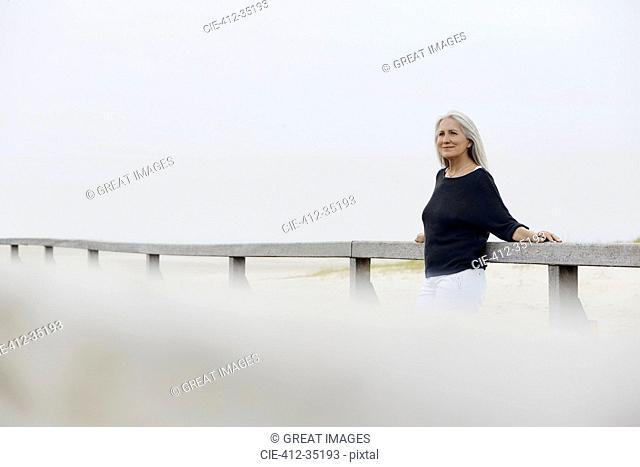 Confident senior woman leaning on beach boardwalk railing