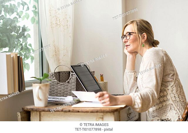 Woman sitting at desk and contemplating