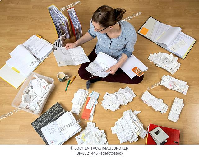 Woman sorting documents, records, invoices and receipts on the ground, for the tax return