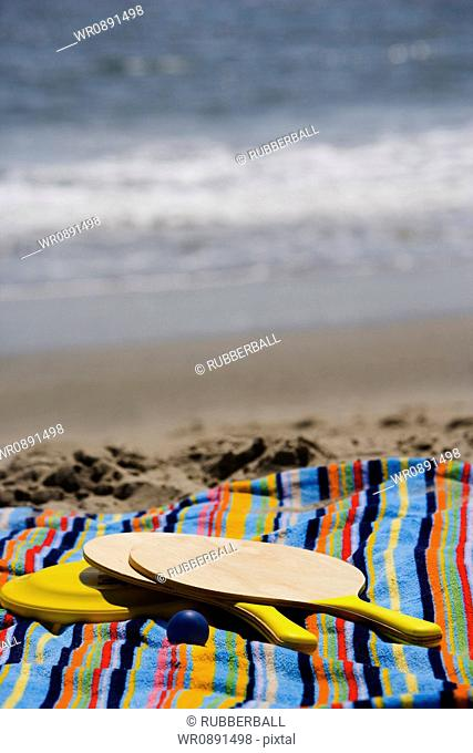 Close-up of paddleball rackets, ball and a Frisbee on a towel