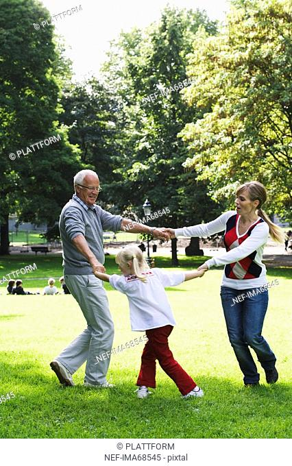 Woman senior man and girl playing in the park Sweden