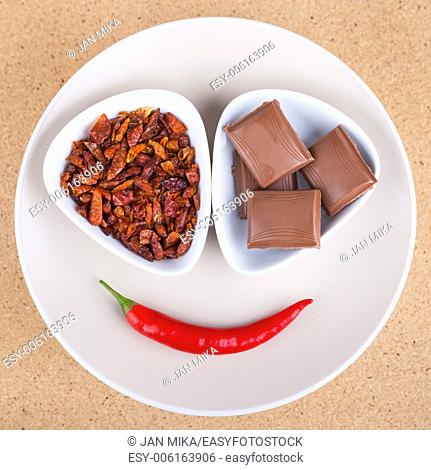 Red hot chili peppers with chocolate on plate, over light wooden background