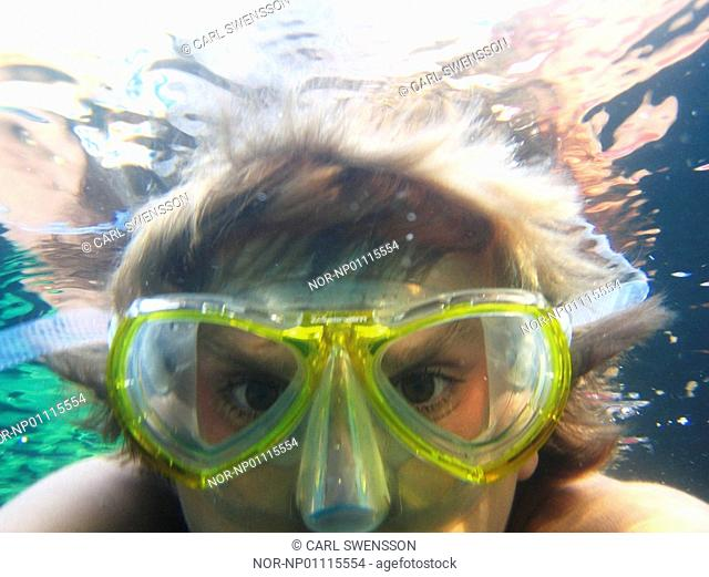 A teenager underwater with a diving mask