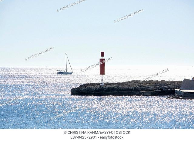 Sailboat and pier with inlet on a bright sunny day in December in Mallorca, Spain