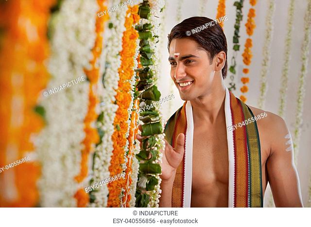 Smiling groom looking through garlands