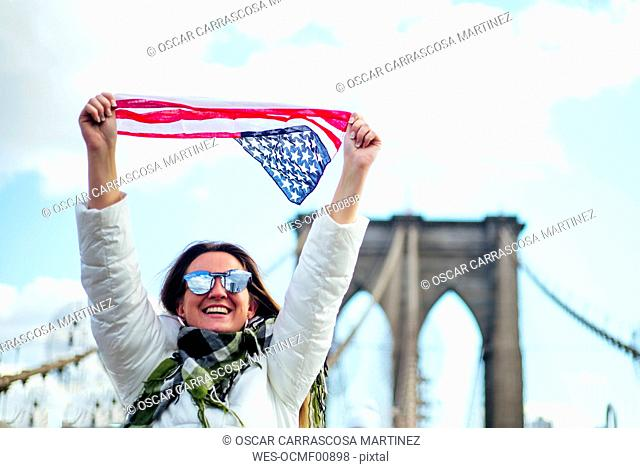 Woman standing on Brooklyn Bridge holding aloft the American flag, New York, United States