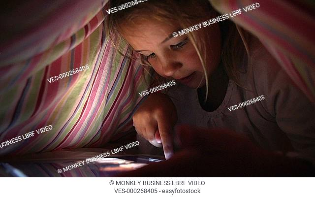 Girl Hiding under duvet looking at digital tablet.Shot on Sony FS700 in PAL format at a frame rate of 25fps