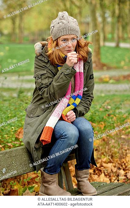 Coughing woman sitting outside on a park bench