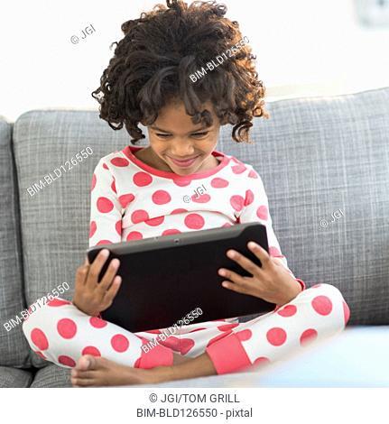 Close up of African American girl in pajamas using digital tablet