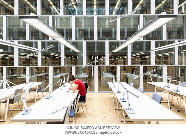 Woman sitting at study table in the reading room. Scientific Information Centre & Academic Library, Katowice, Poland. Architect: HS99 , 2012