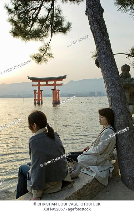 women along the sea near itsukushima shrine torii temple gate, miyajima island, near Hiroshima Japan