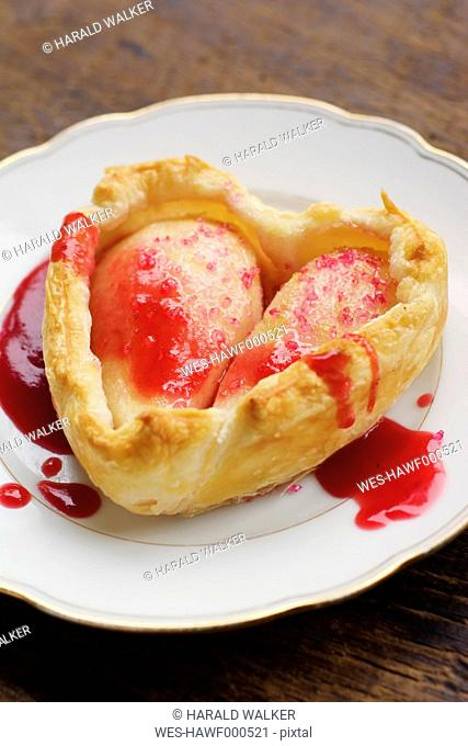 Pear heart tarts with red current sauce on plate