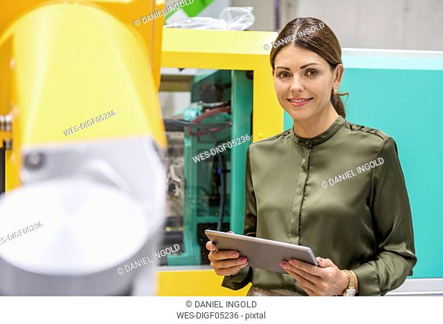 Businesswoman checking industrial robot in high tech company