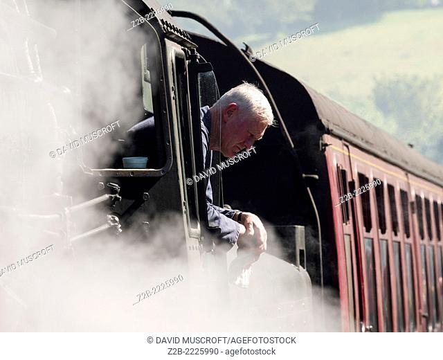 Train driver of a vintage steam locomotive at Grosmont station on the North Yorkshire Moors Railway, near Whitby, North Yorkshire, UK