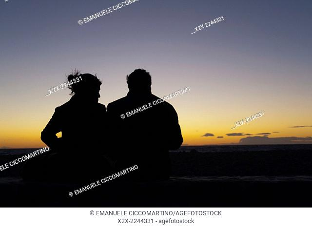 Couple watching sunset, Es Codolar Boulder beach, Eivissa, Ibiza, Balearic Islands, Spain, Mediterranean, Europe