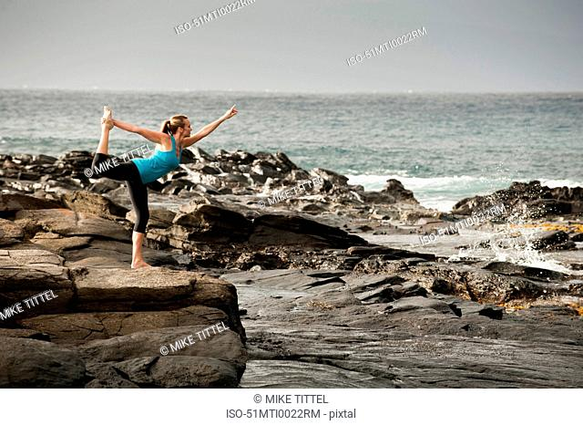 Woman practicing yoga on rock formation