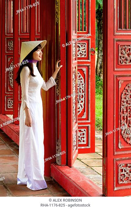 A woman in a traditional Ao Dai dress and Non La conical hat in the Forbidden Purple City of Hue, UNESCO World Heritage Site, Thua Thien Hue, Vietnam, Indochina