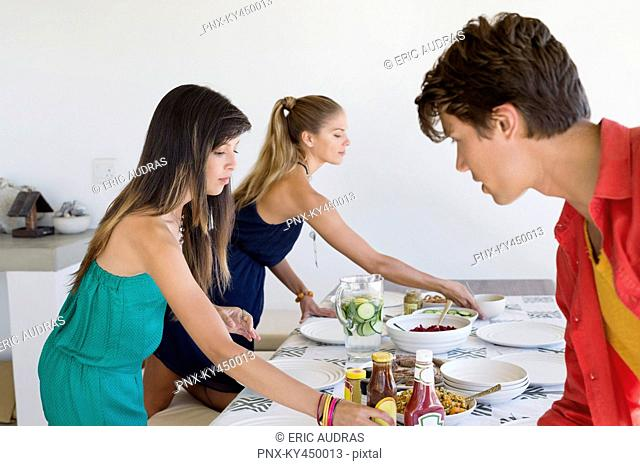 Friends setting a dining table