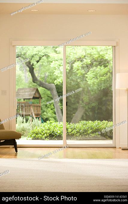 Empty living room with view of back yard through double sliding door