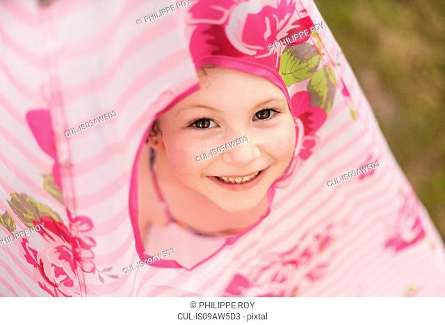 High angle view of girl peeking out of teepee, looking at camera smiling