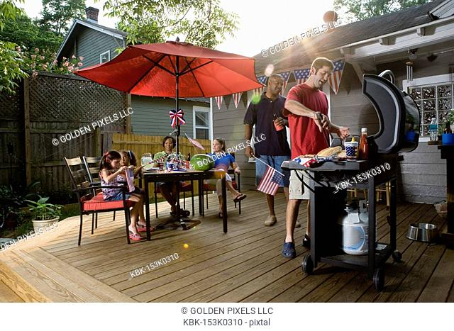 Two families on backyard patio celebrating 4th of July