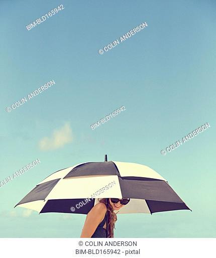 Caucasian woman holding parasol under blue sky