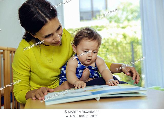 Mother and baby daughter looking at childrenƒ.s book