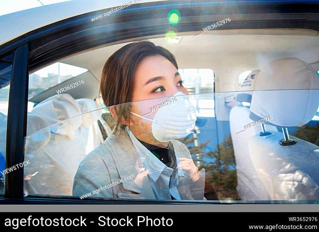 The young woman wearing a mask by car