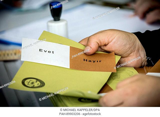 """An election assistant at a polling station in Istanbul, Turkey, holds a ballot for the constitutional referendum on which the words """"""""Evet"""""""" (yes) and..."""