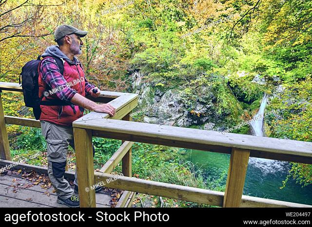 Hiker man in a viewpoint close to a river. Urederra river source. Urbasa-Andia Natural Park. Navarre, Spain, Europe