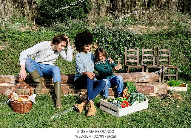 Happy family taking a break after harvesting vegetables, taking selfies
