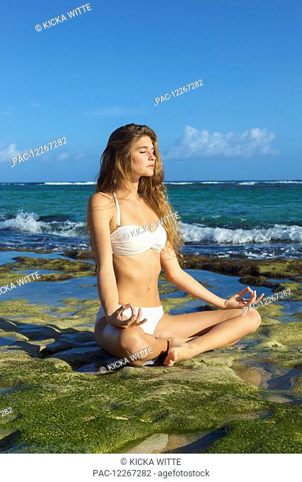 Young woman on the beach in a yoga pose; Kauai, Hawaii, United States of America