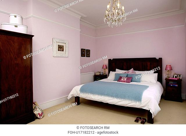 Chandelier Above Bed With White Linen And Turquoise Throw In Pastel Pink Bedroom
