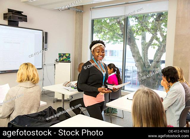 Smiling female community college instructor leading lesson in classroom