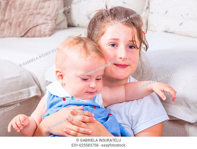 Big sister holding her 1 year old baby sister