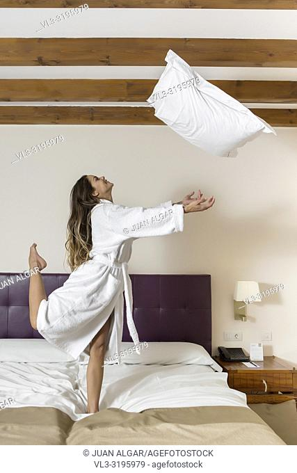 Side view of charming female jumping in bathrobe on bed and throwing up pillow in hotel room