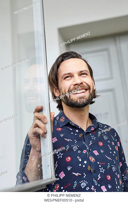 Portrait of laughing man at open window