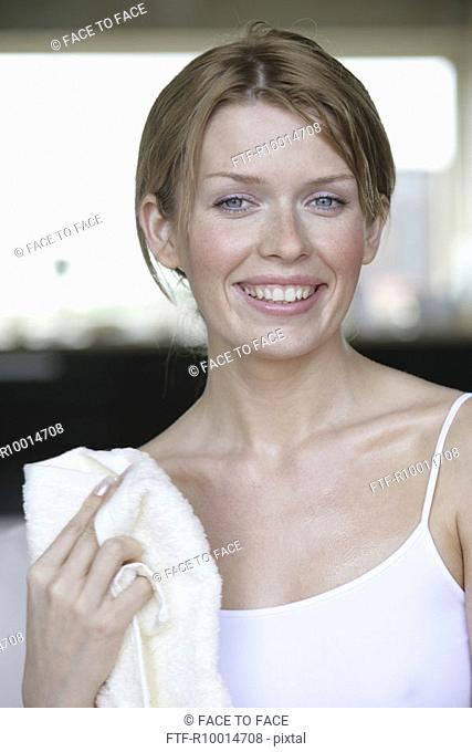 A blonde woman wiping her body with a towel