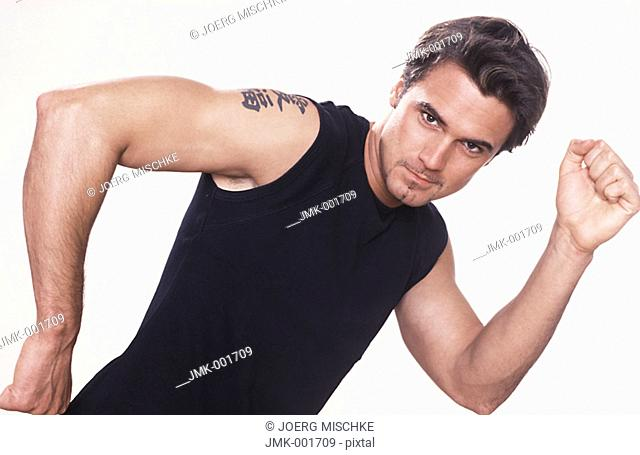 Portrait of a young man, 20-25 25-30 30-35 dark-haired, masculine, powerful, strong, athletic and beautiful in a black sleeveless tee-shirt