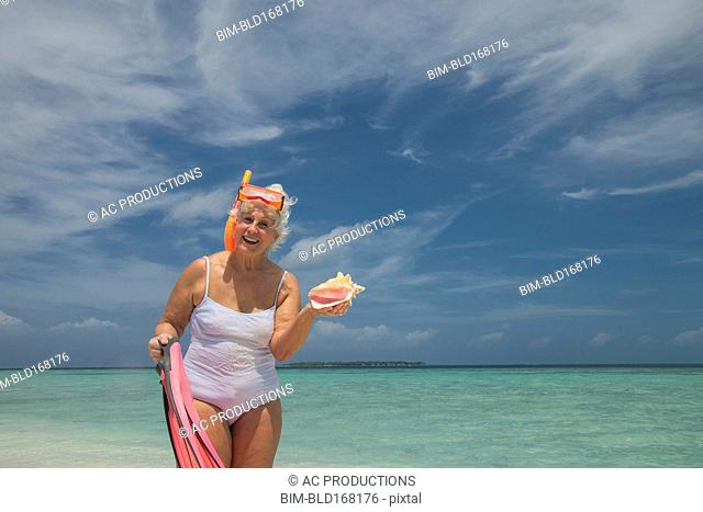 Older Caucasian woman holding conch shell on beach