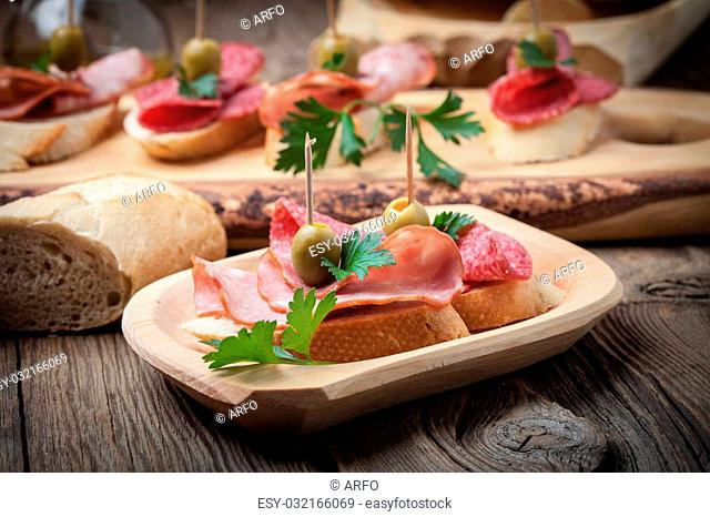 Spanish cuisine. Tapas with sliced sausage, salami, olives and parsley on a wooden table